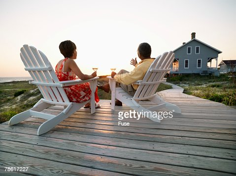 Couple Drinking Wine on Jetty at Sunset