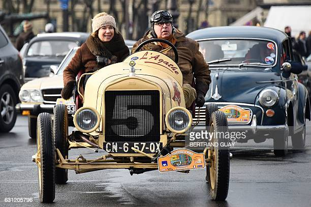 A couple drive their vintage car in the streets of Paris on January 8 2017 during the 17th edition of the 'Traversee de Paris en Anciennes' the...