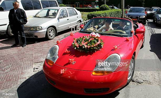 A couple drives a Porsche roadster to their wedding ceremony on September 9 2006 in Beijing China A wedding craze sweeping China is causing a boom...