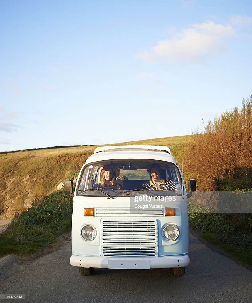 Couple driving camper van along coastal road. : Stock Photo