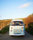 Couple driving camper van along coastal road.