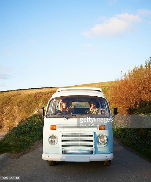 Couple driving camper van along coastal road.