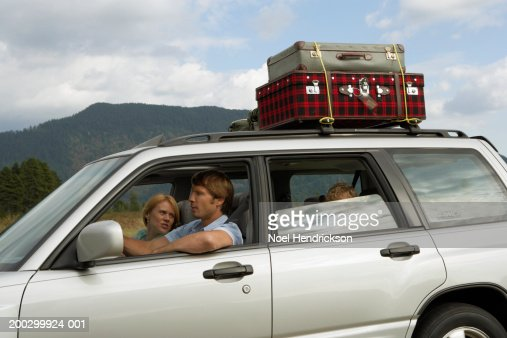 Couple driving car, side view, mother looking over shoulder to son (5-7 years) in rear seat : Stock Photo
