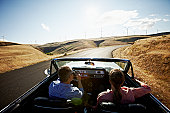 Couple driving convertible in desert at sunset