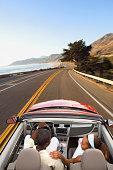 Couple driving convertible on coastal road