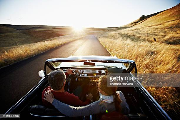 Couple driving convertible on empty road at sunset