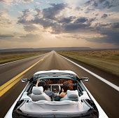 Couple driving convertible through remote area