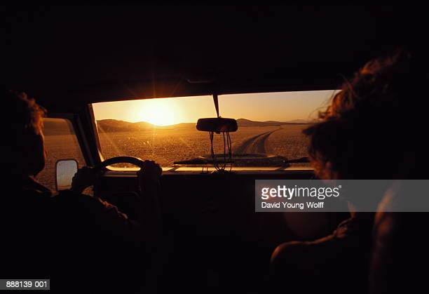 Couple driving down valley at sunset, Kaokoveld, Namibia