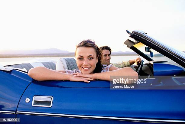 Couple Driving in a Blue Convertible Across the Desert, Woman Leaning on Car Door