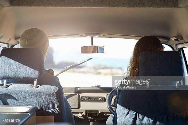 Couple driving in camper van.