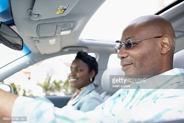 Couple driving in car, side view, close-up (focus on man)