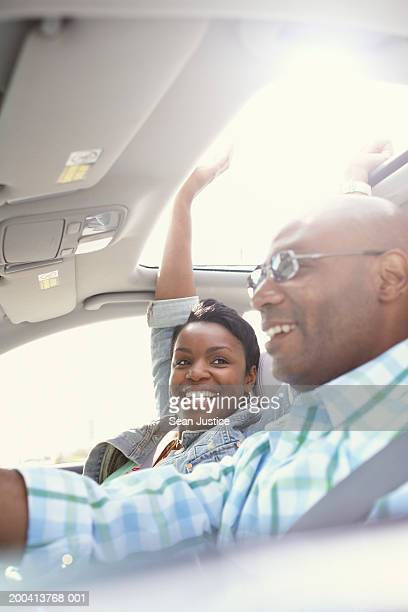 Couple driving in car, woman sticking hand out of sun roof, close-up