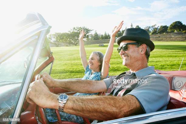 Couple driving in classic convertible