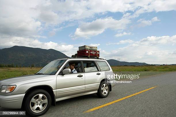 Couple driving sports utility vehicle on rural road