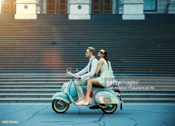 Couple driving vintage scooter
