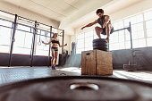 Fit young man box jumping with woman exercising with skipping ropes at a cross training style gym. Couple during intense workout session at health club.