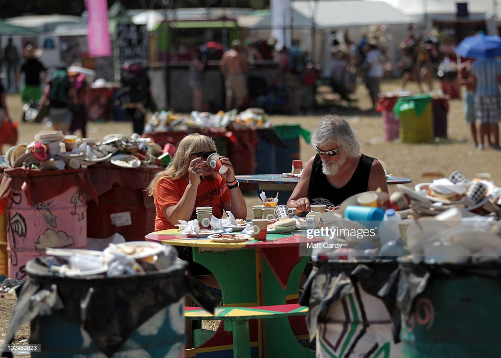 A couple eat breakfast while seated at a table surrounded with overflowing litter bins as festivalgoers leave the 40th Glastonbury Festival at Worthy...