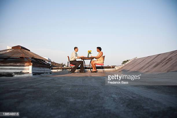 A couple eating a meal on a rooftop terrace