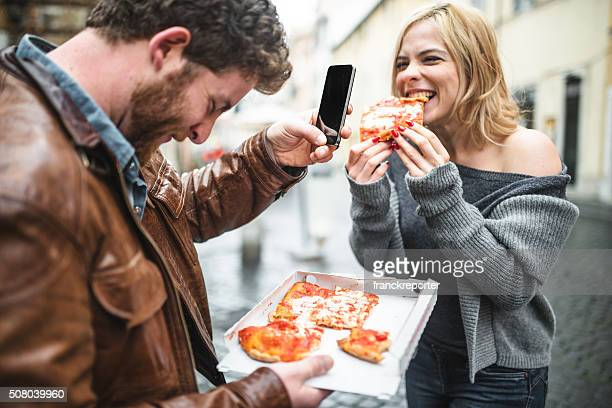 couple eating a pizza in italy and taking pictures
