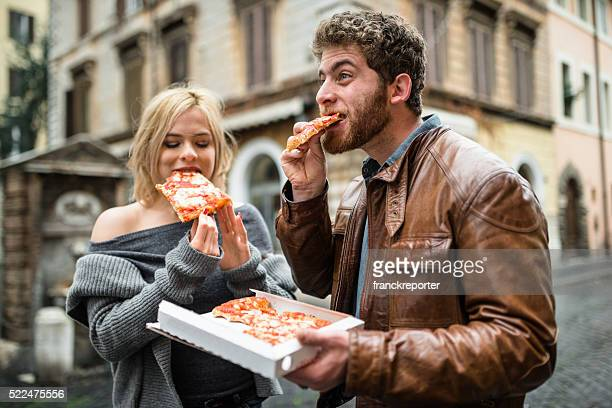couple eating a pizza in italy