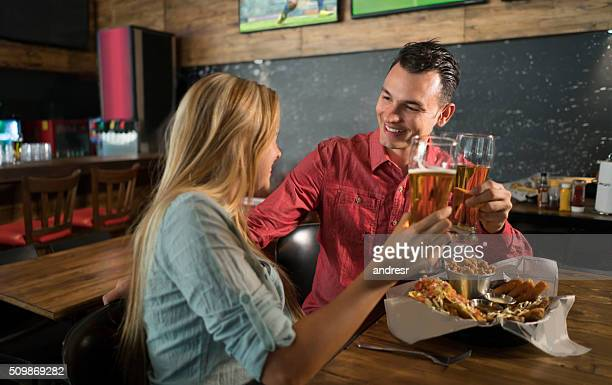 Couple eating and drinking on a date at the bar