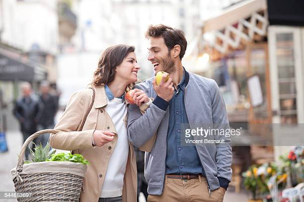 Couple eating apple in the street