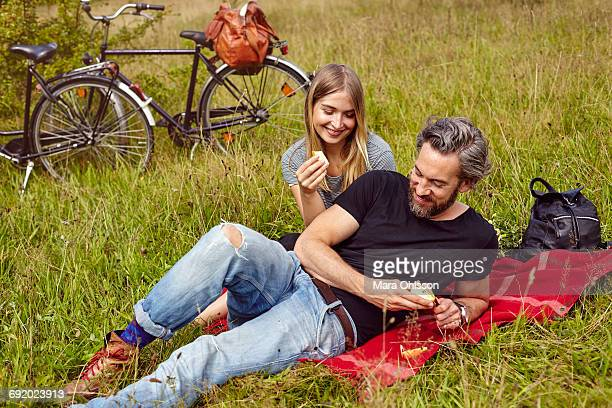 Couple eating apples at picnic in rural field