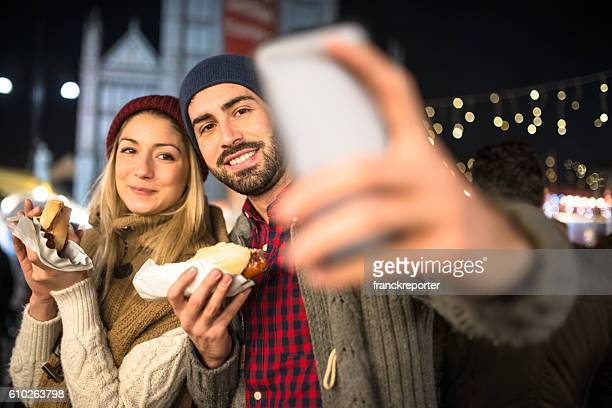 couple eating at the christmas market and take a selfie