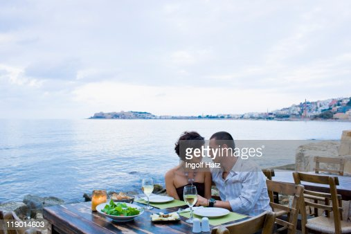 Couple eating at waterfront cafe : Stock Photo