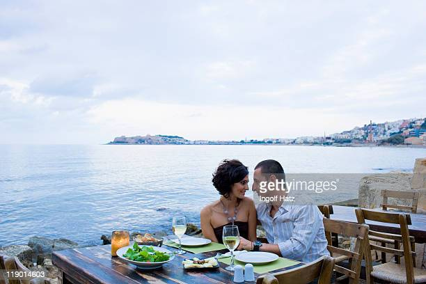 Couple eating at waterfront cafe