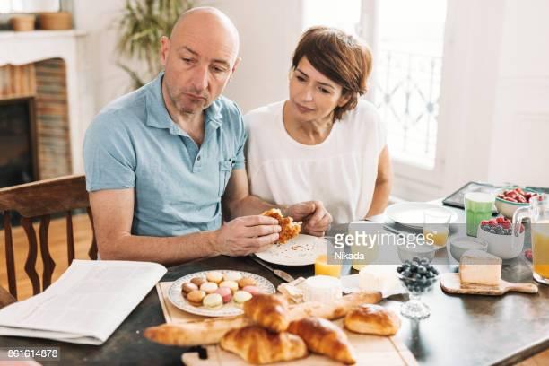 Paar frühstücken und Zeitung lesen