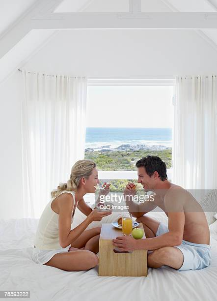 A couple eating breakfast in bed