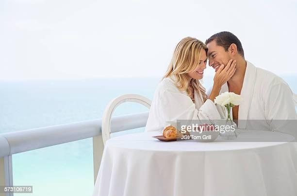 Couple eating breakfast on balcony