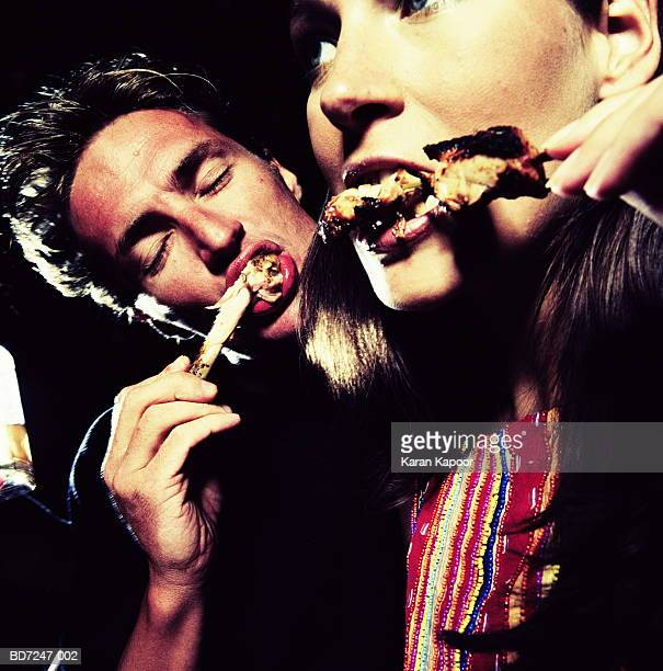 Couple eating chicken legs, close-up