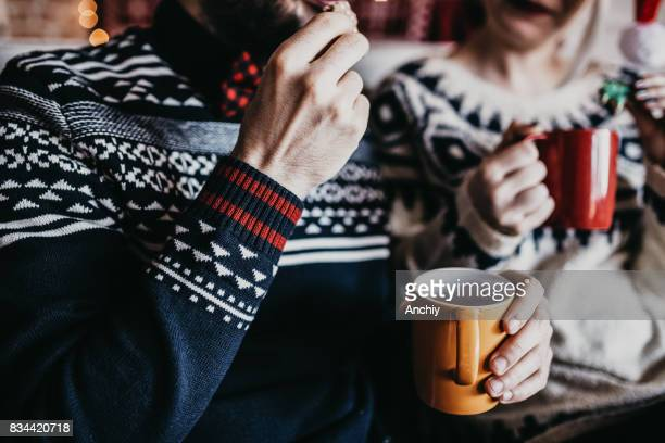 Couple eating Christmas cookies, close up on hands