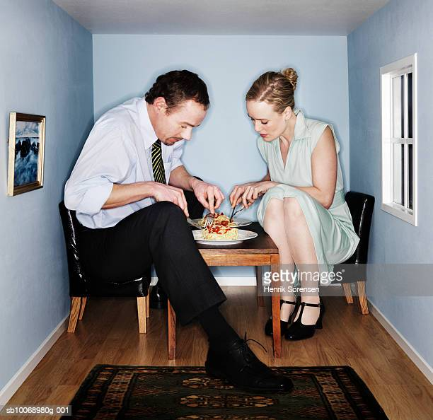 Couple eating dinner in small dining room