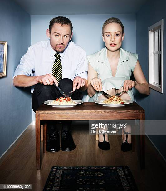 Couple eating dinner in small dining room, portrait