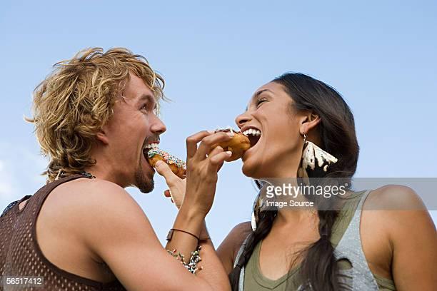 Couple eating doughnuts