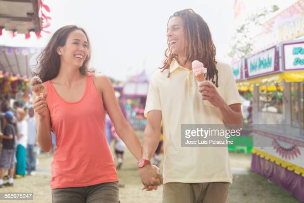 Couple eating ice cream at amusement park