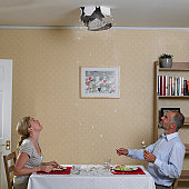 Couple eating meal with foot coming through ceiling