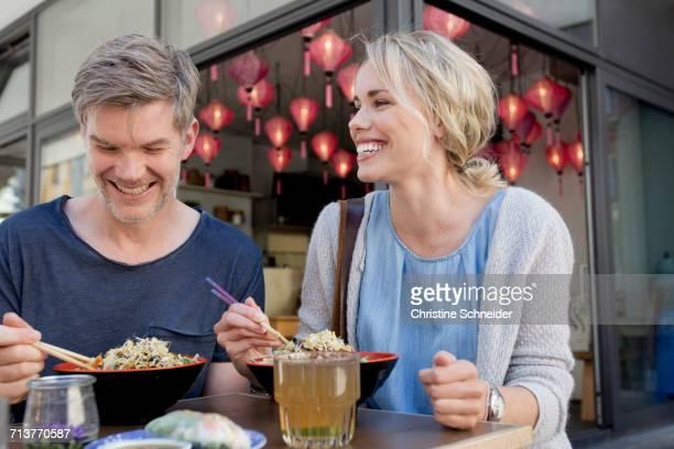 Couple eating noodles at city sidewalk cafe