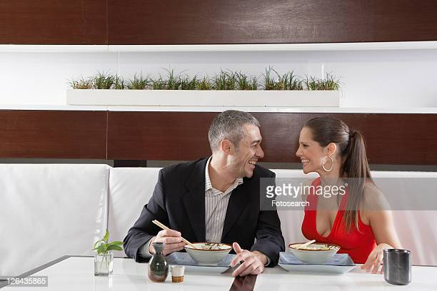 Couple eating noodles in restaurant