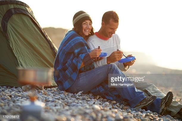 Couple eating outside tent on pebble beach.