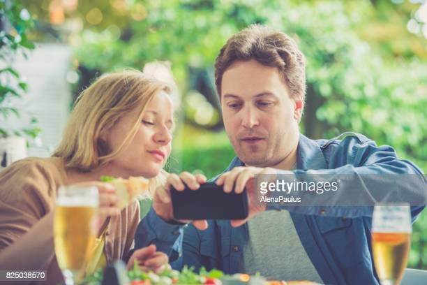 Couple eating pizza and taking food photos outdoors