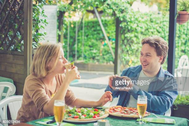 Couple eating pizza and taking selfies outdoors