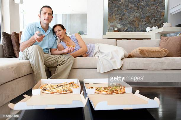 Couple eating pizza in living room