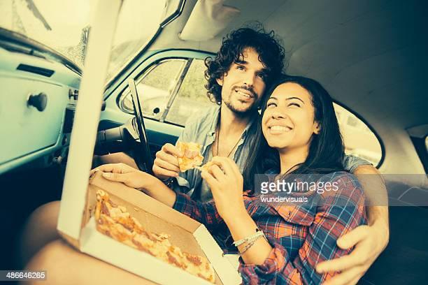 Casal comer pizza em retro Carro
