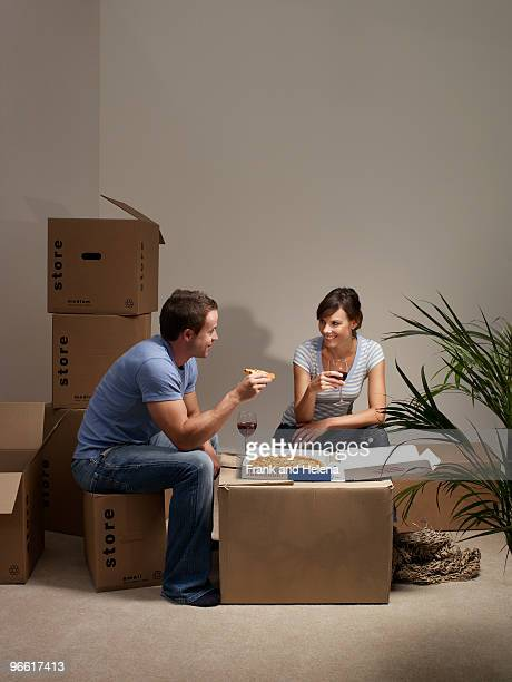 Couple eating pizza on cardboard box