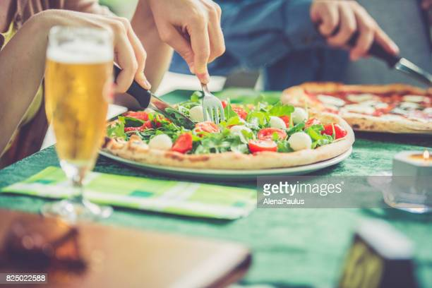 Couple eating pizza outdoors close up