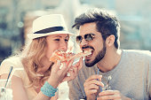 Couple eating pizza snack outdoors.